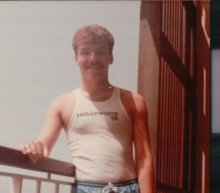 John in his 'Hollywood '83' tank top, however this photo might have been snapped in Puerto Rico. What of it?